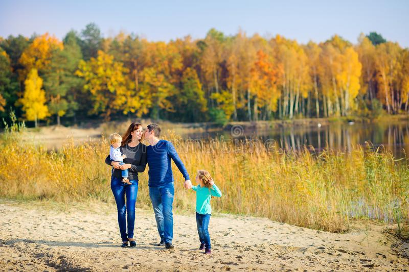 Family walking in beautiful autumn park near lake royalty free stock photo