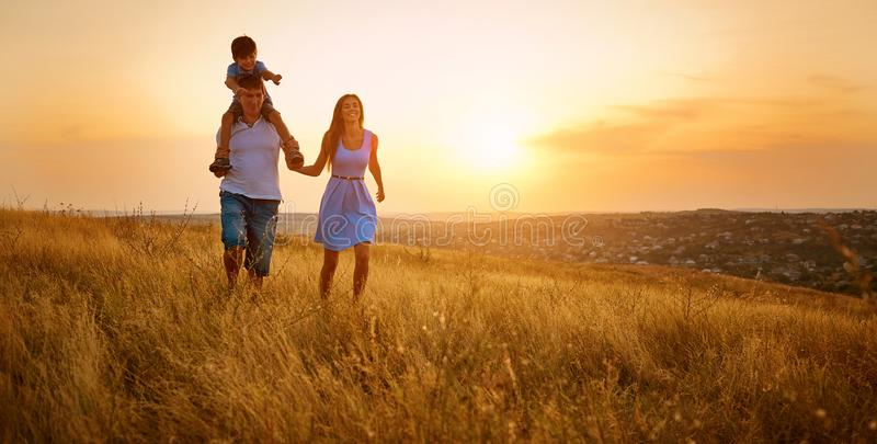 Happy family walking on field in nature at sunset stock photos