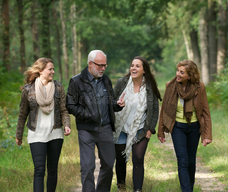 Happy family walking through the forest together royalty free stock photo