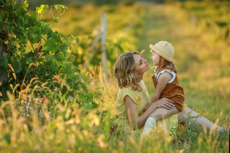 A Happy family walking history. mother and baby hugging in a meadow yellow flowers on nature in summer.  stock image