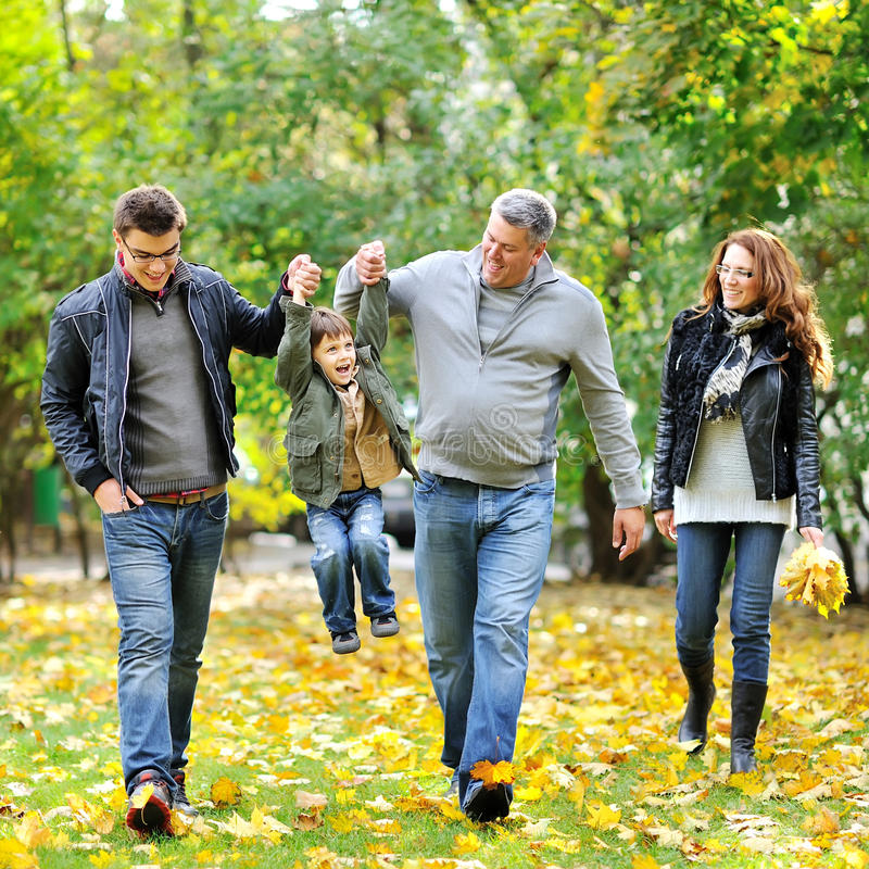 Happy family walking together in a park stock images