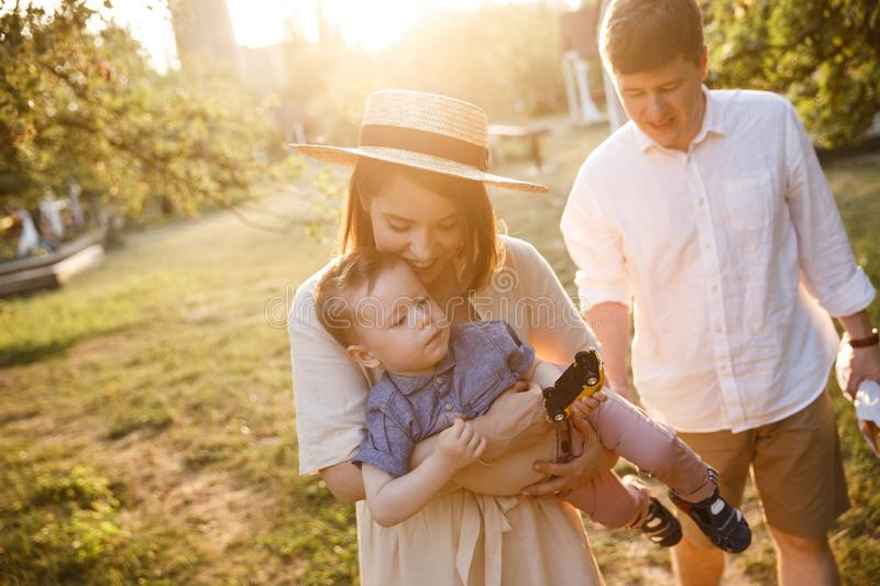 Happy family is walking togther in garden. Mother is playing with her son and carring him on hands. She is smiling royalty free stock photo