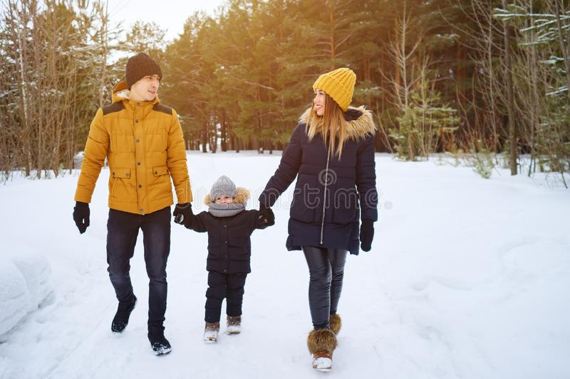 Happy family walking in winter day in forest royalty free stock photography