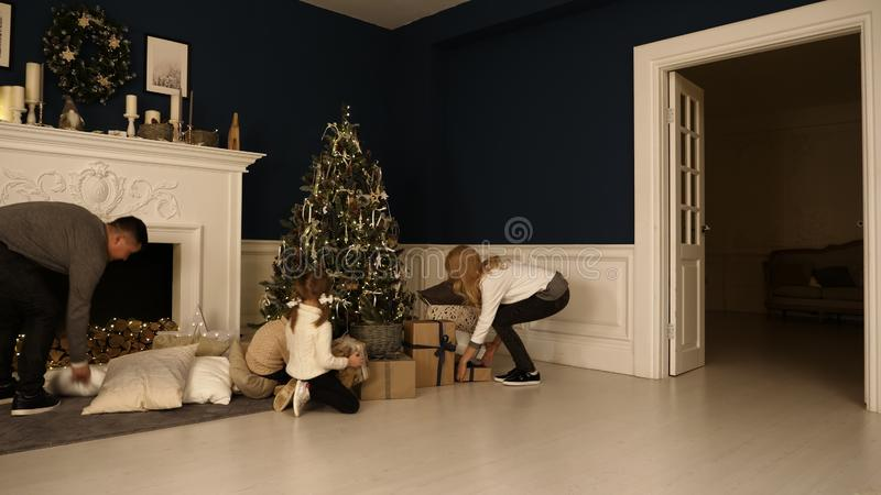Happy family walks in living room to check the presents under the Christmas tree. royalty free stock photography