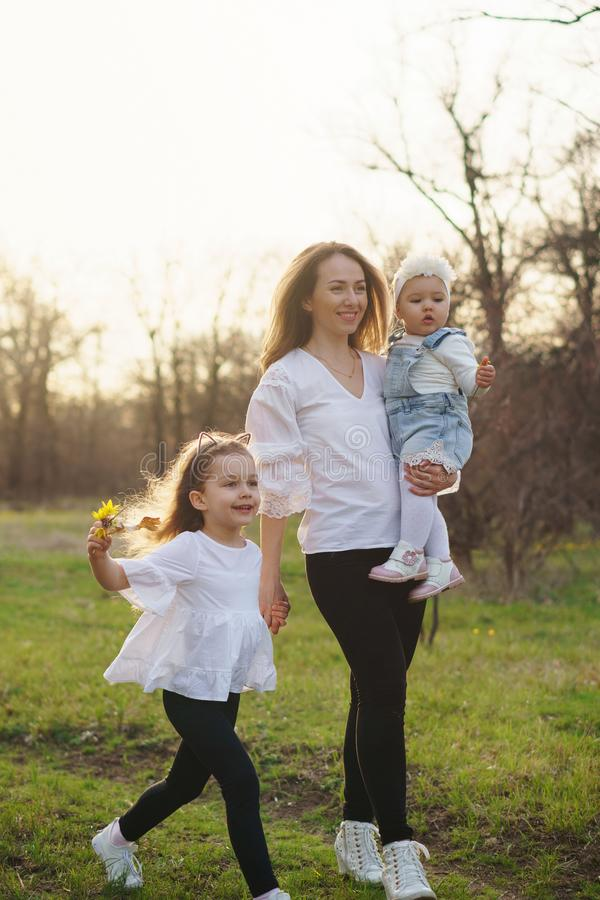 Happy family walks in the spring meadow. Happy young family on a walk in the spring meadow. Mom holds toddler in her arms. Girls in casual wear. Family look stock photography