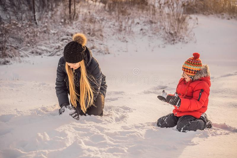 Happy family in warm clothing. Smiling mother and son making a snowman outdoor. The concept of winter activities stock image