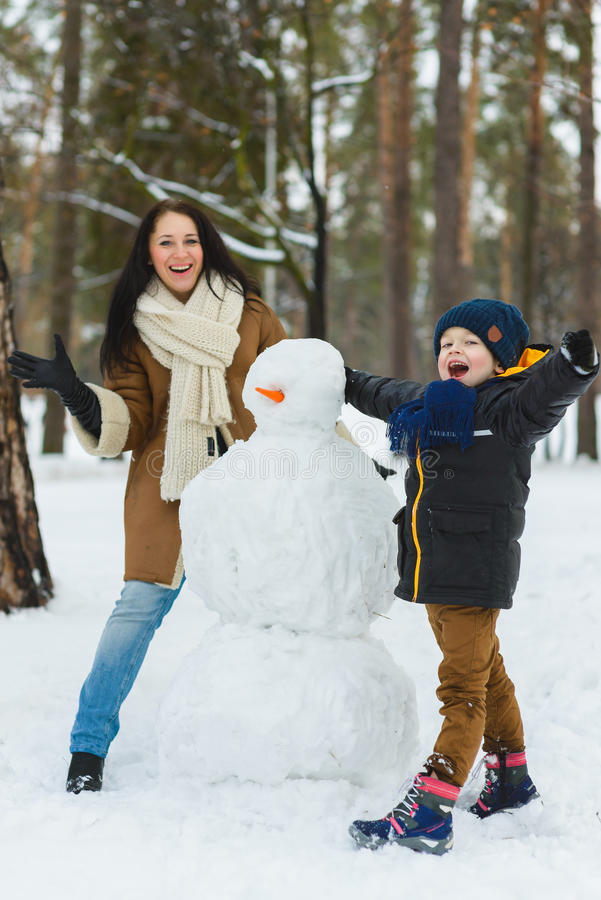 Happy family in warm clothing. Smiling mother and son making a snowman outdoor. The concept of winter activities royalty free stock images