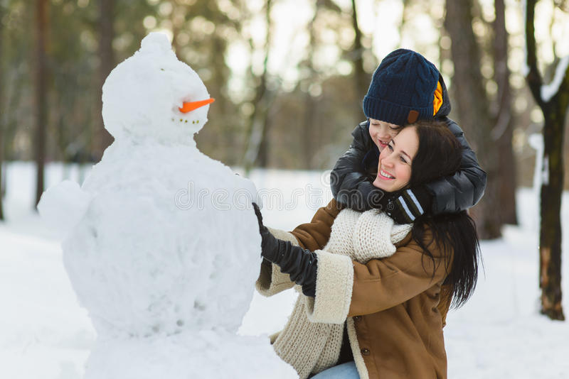 Happy family in warm clothing. Smiling mother and son making a snowman outdoor. The concept of winter activities.  stock photos