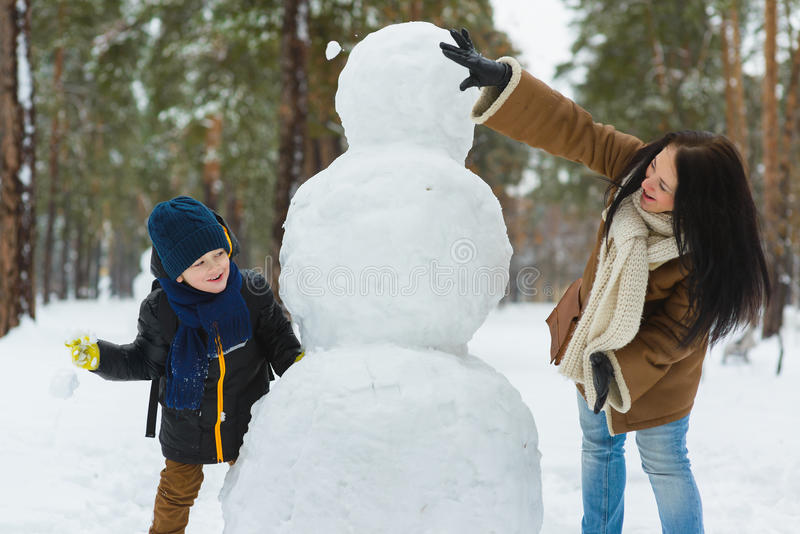 Happy family in warm clothing. Smiling mother and son play snowballs next to a snowman outdoor. The concept of winter stock image