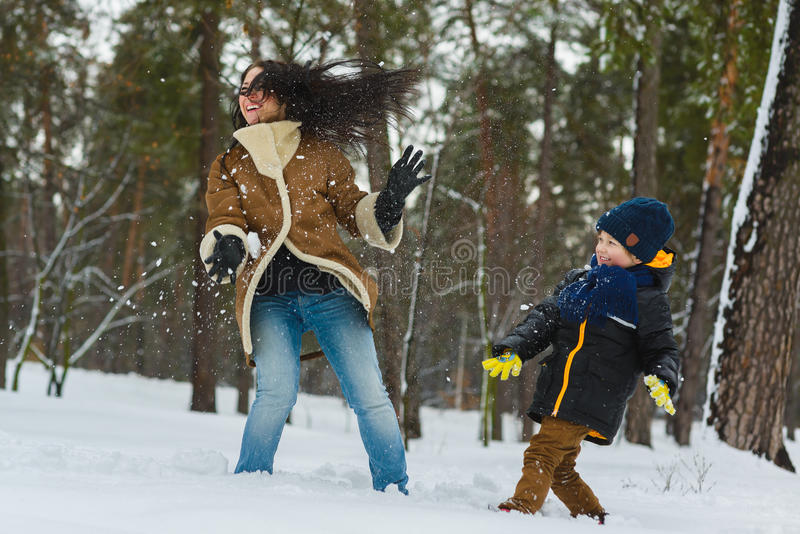 Happy family in warm clothing. Smiling mother and son play snowballs outdoor. The concept of winter activities stock photography