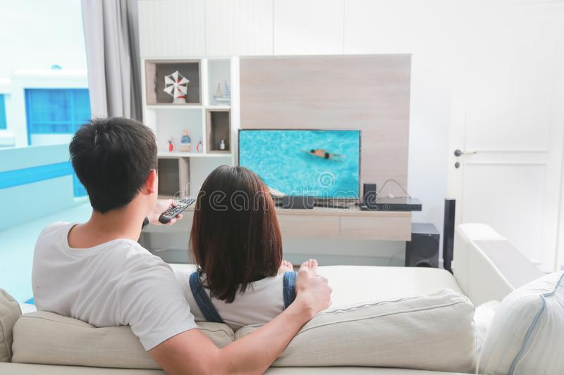 Happy family watches television while sitting on the sofa. royalty free stock photos