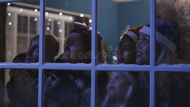 Happy family watching fireworks through window royalty free stock photos