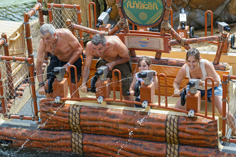 Happy family during the water gun battle on the water attraction Angkor. Theme park Port Aventura, Salou, Catalonia, Spain. stock photo