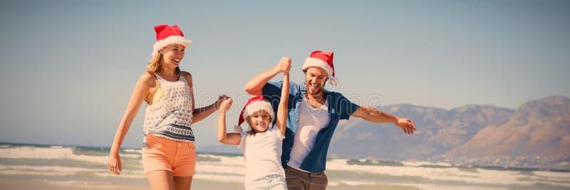 Happy family wearing Santa hat while enjoying at beach stock photos