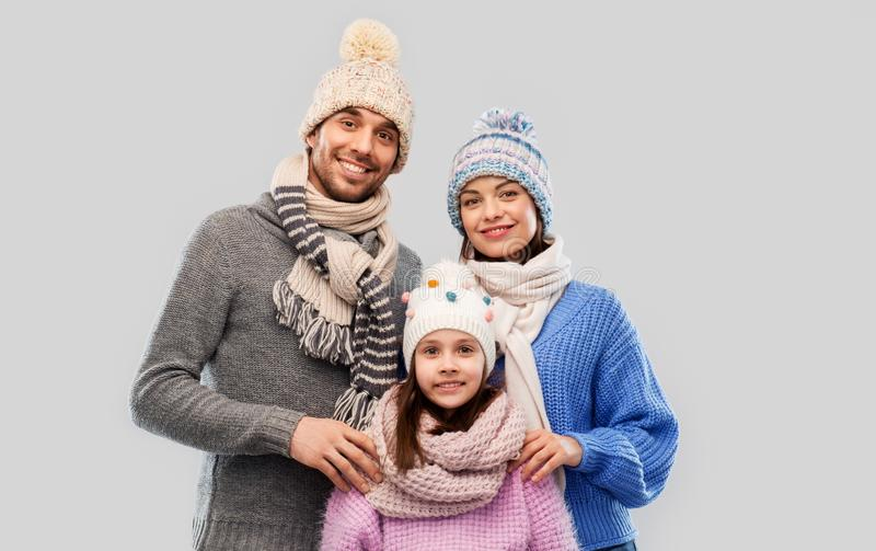 Happy family in winter clothes on grey background stock images