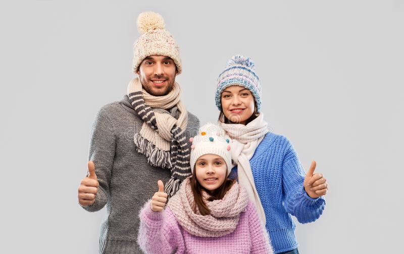 Happy family in winter clothes on grey background royalty free stock photos