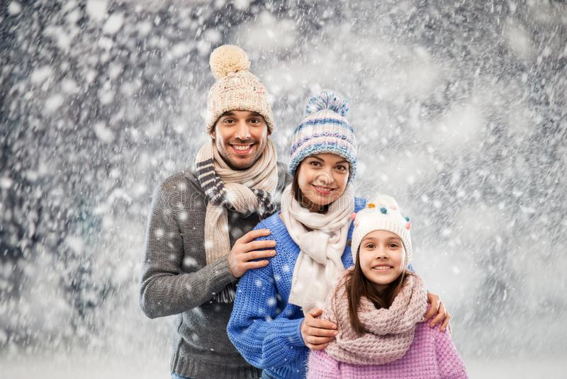 Happy family in winter clothes on snow background stock image