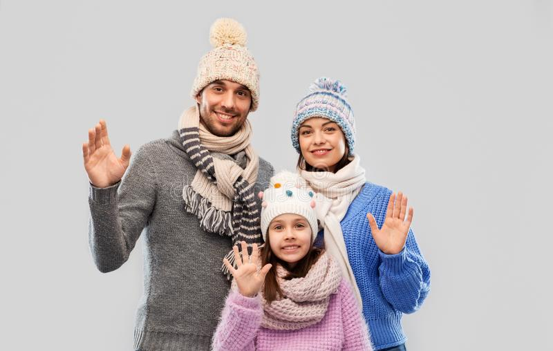 Happy family in winter clothes waving hands stock images