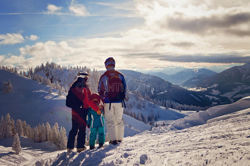 Happy family in winter clothing at the ski resort stock photography