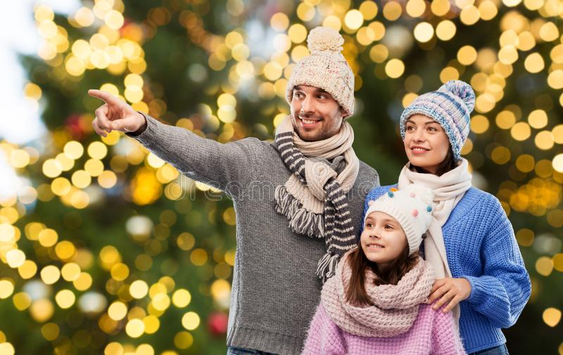 Happy family in winter hats over christmas lights stock photo