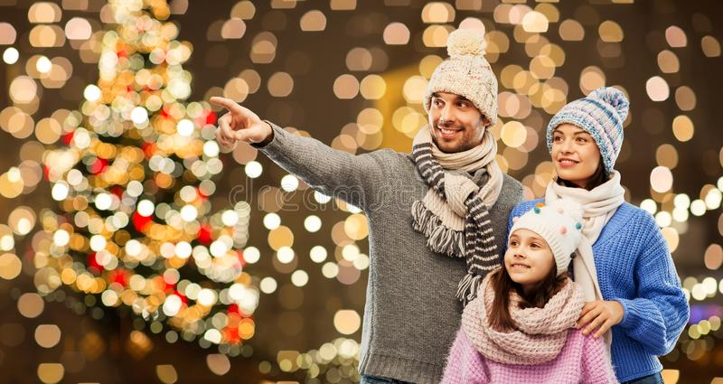 Happy family in winter hats over christmas lights royalty free stock photos