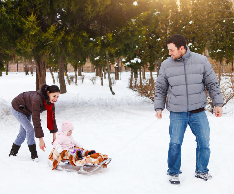 Happy family in winter park. Baby on the sled In the snow royalty free stock image