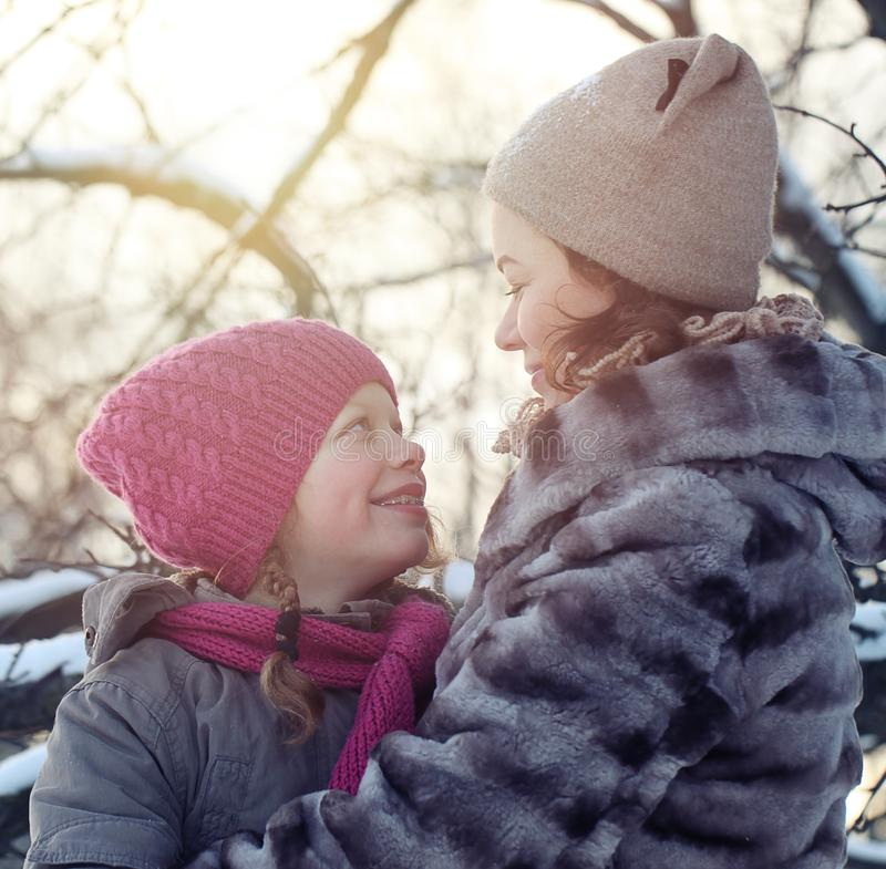Happy Family in Winter Park. Mother and Daughter looking at each other stock photography