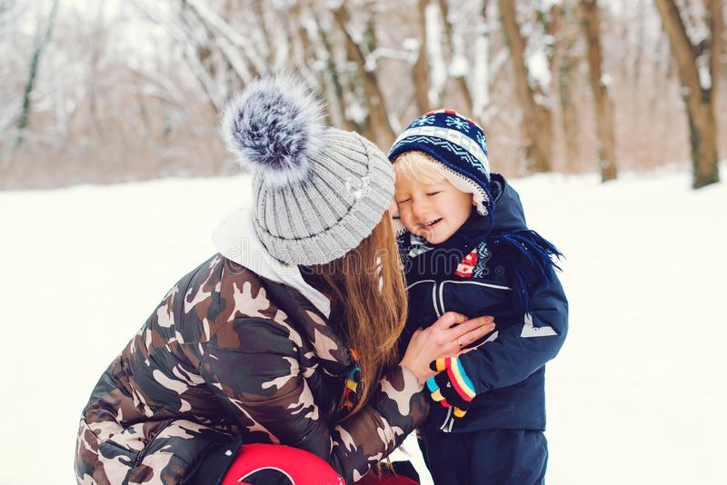 Happy family on a winter walk. Young mother and baby boy playing in snow. Frost winter snowy season. Happy child with mom enjoing stock photography
