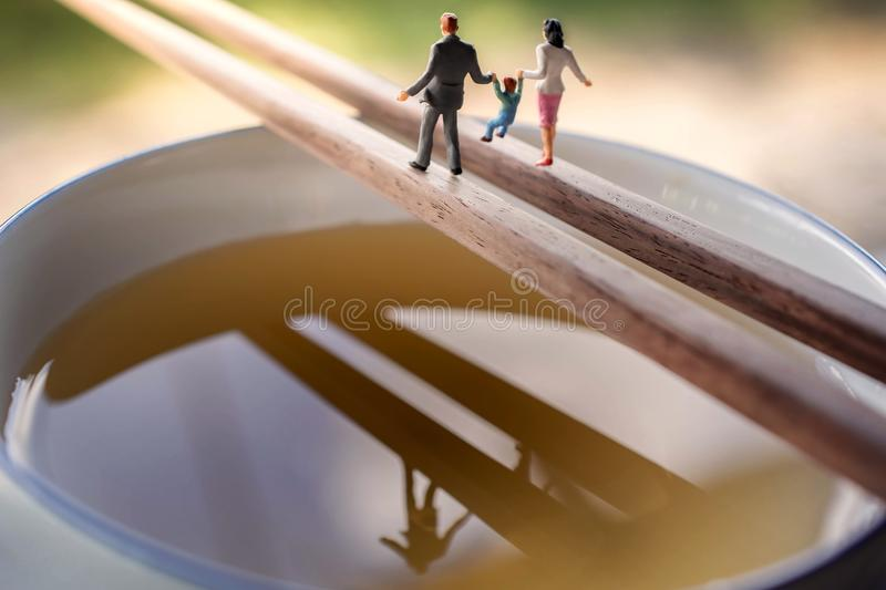 Happy Family with Work Life Balance Concept. present by Miniature Figure of Father, Mother and Son with Happiness Moment. Walking. On Chopstick over a Soup Bowl stock photography