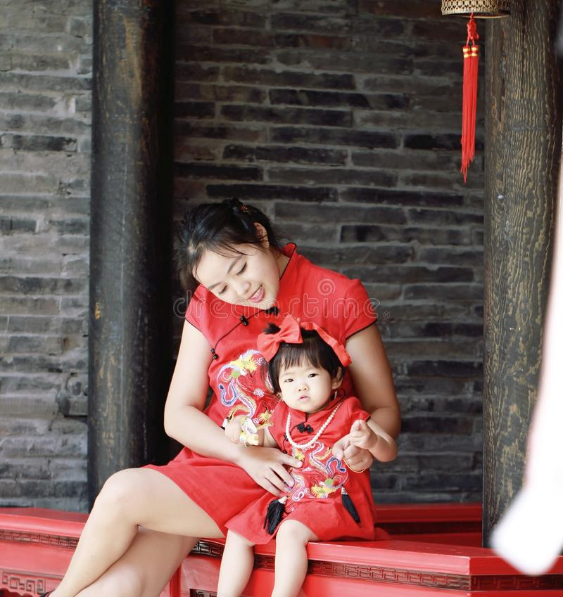 happy family young Chinese mother has fun with baby in China traditional cheongsam stock image