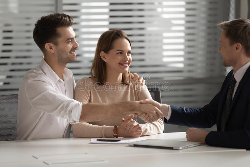 Happy family young couple shaking hands with financial advisor. stock image