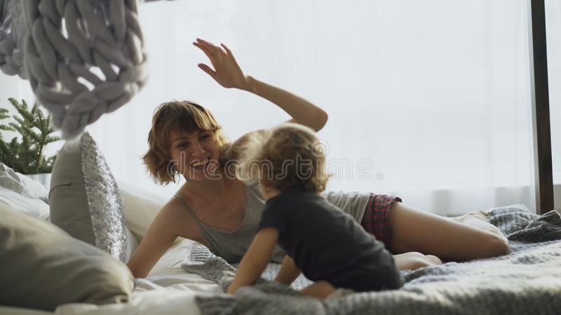 Happy family with young cute daughter playing in bed at home royalty free stock photography