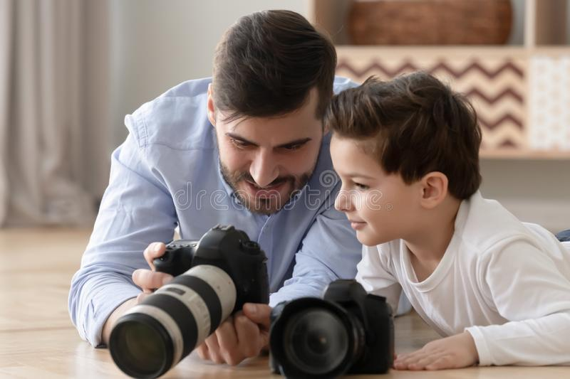 Happy dad and kid son play digital cameras at home. Happy family young dad and cute little son holding modern digital cameras playing on warm floor at home royalty free stock images