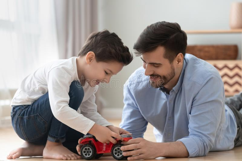 Happy dad and kid son play toy car at home. Happy family young dad and cute little son play toy car on warm heated floor at home, small preschool child boy royalty free stock photo