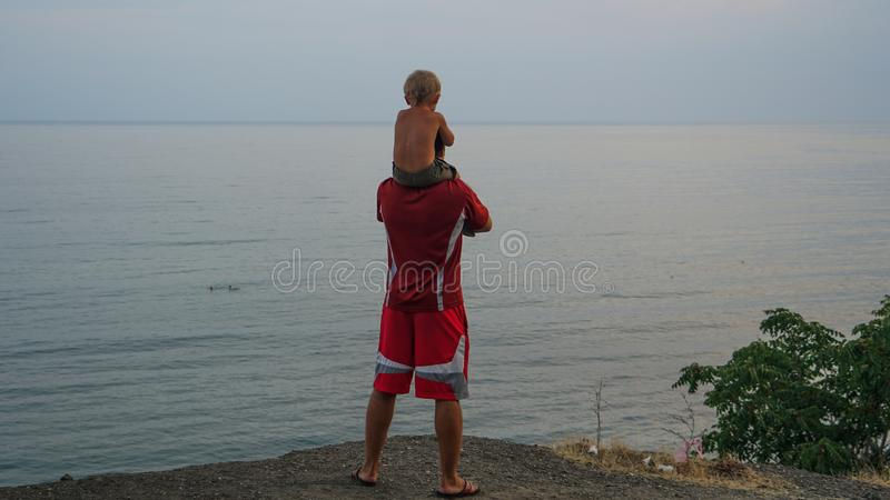 Happy family: Young father with his little child sitting on father`s shoulders royalty free stock photography