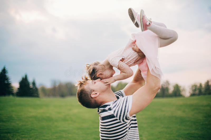 Happy family. Young father playing silly with his daughter lifting her up royalty free stock photography