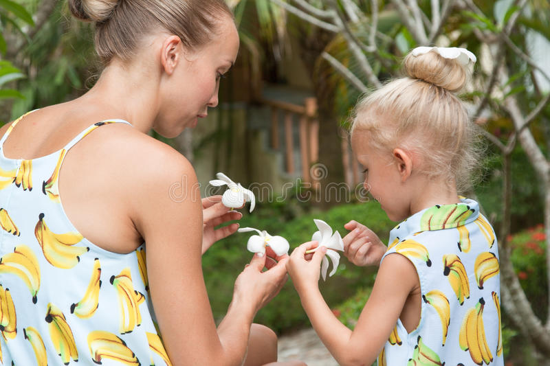 A happy family. Young mother and daughter sitting in a tropical garden with flowers in their hands. stock photography