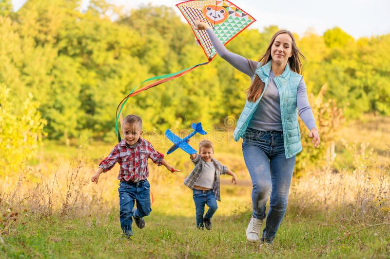 Happy family of young mother and its kids launch a kite on nature at sunset. Family holidays royalty free stock images