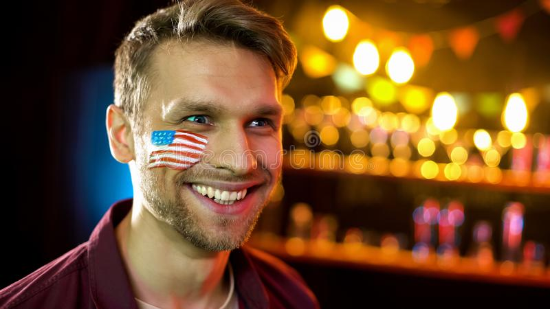 Happy fan of american sport smiling, watching hockey in pub, leisure activity stock photos