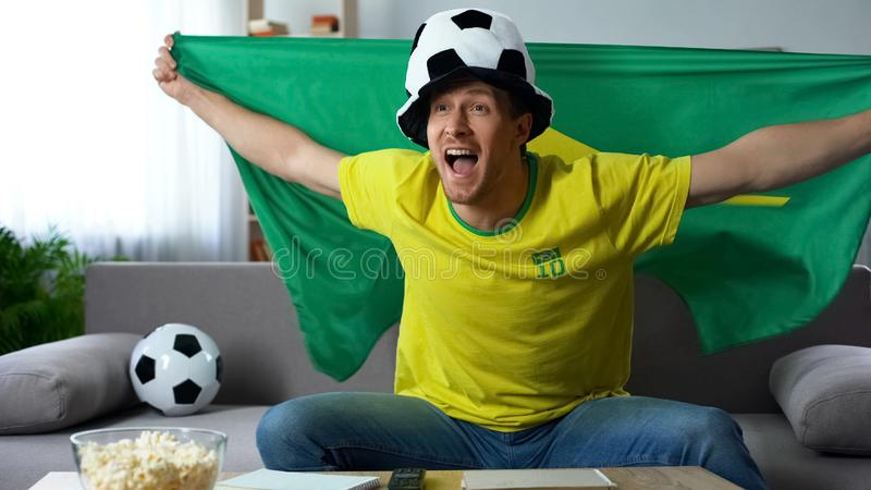 Happy fan cheering Brazil team celebrating successful match, watching game on tv. Stock photo stock images