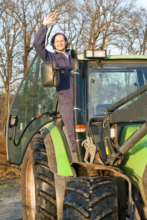 Happy farm hand. A happy farm hand standing in the door opening of a big tractor, waving at the camera stock photo