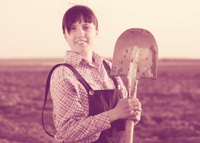 Happy farmer in field. Happy female farmer with shovel in field stock photos