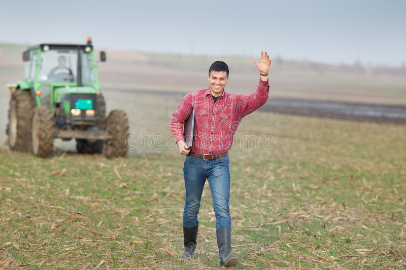 Happy farmer on field. Happy young farmer waving with hand on farmland with tractor in background stock images