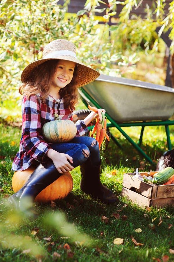 Happy farmer kid girl picking autumn vegetable harvest in the garden stock photo