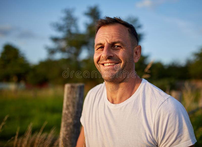 Happy farmer at sunset. Evnironmental portrait royalty free stock photography