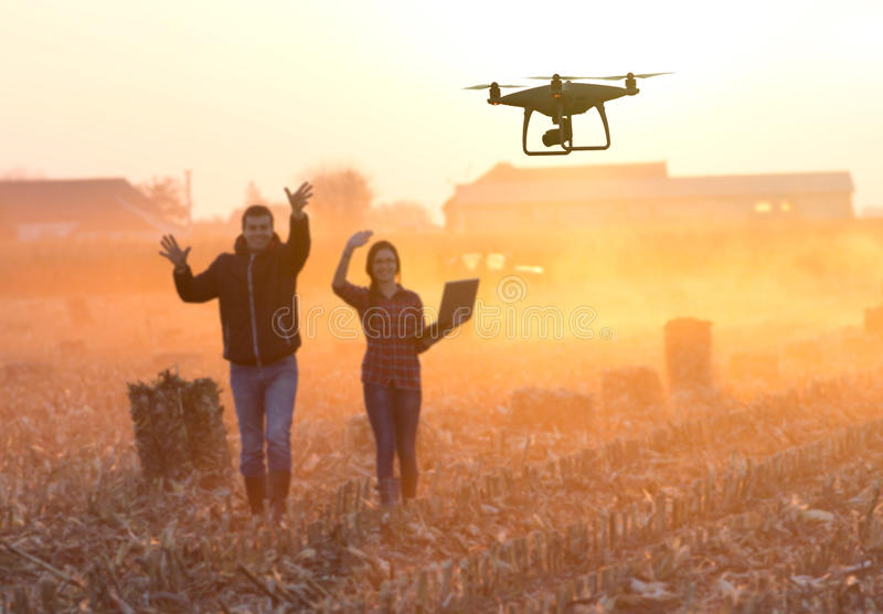 Happy farmers waving hands to drone royalty free stock image