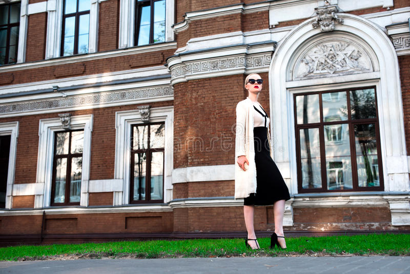 Happy Fashion blonde european elegant Woman with red lips and white skin Standing at the Old Red Brick building on green grass. royalty free stock images