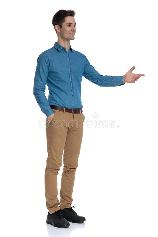 Happy fashion man smiling and presenting to side stock image