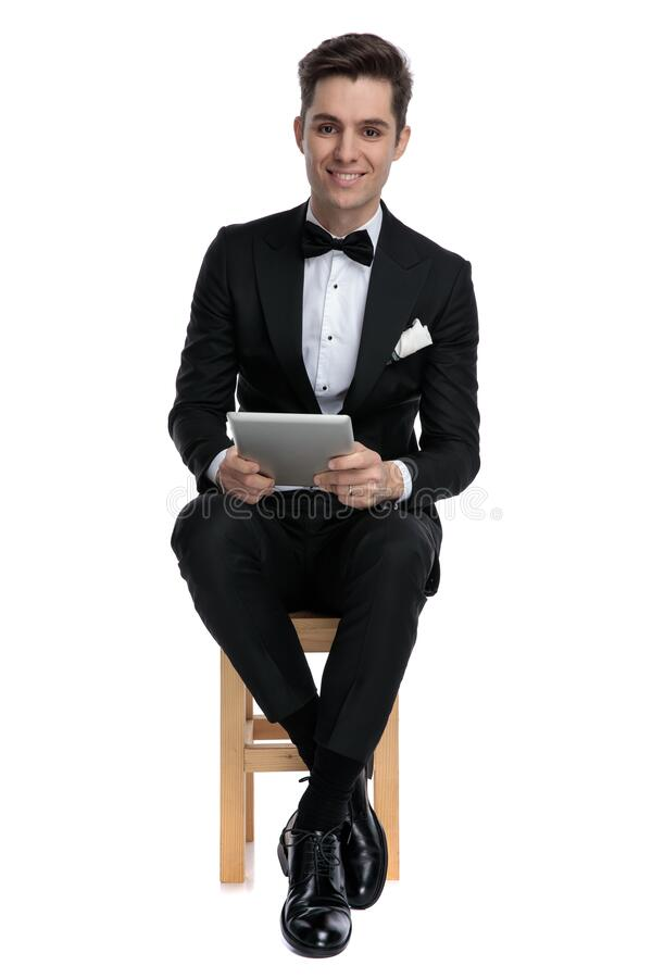 Happy fashion model in tuxedo holding tab stock photography