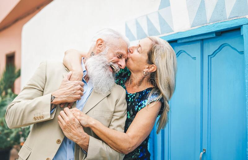 Happy fashion senior couple dating outdoor - Mature elegant older people celebrating date of their anniversary. Wife kissing her husband - Concept of love and royalty free stock images